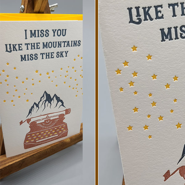 """Letterpress printed A6 folding card. Says """"I miss you like the mountains miss the sky"""" in dark blue. Has yellow stars below that, and a typewriter with mountainscape at the top. The card sits in front of a bright yellow envelope that matches the color of the stars on the card. Both the card and the envelope sit on a small, wooden easel."""