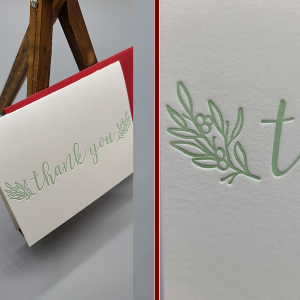 Letterpress printed thank you folding card. Celedon green ink. The image shows the card with a red envelope behind it, sitting on a small wooden easel. There is a second image -split screen- of an up close look at berries and leaves detail.