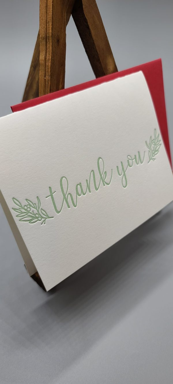 Letterpress printed thank you folding card. Celedon green ink. The image shows the card with a red envelope behind it, sitting on a small wooden easel. Green Letterpress printed folding card