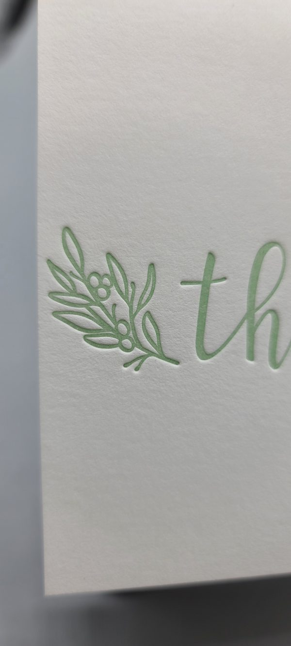 """Detail of leaves and berries up close. Celedon green ink. The image shows the first two letters of the thank you card (""""th"""")"""