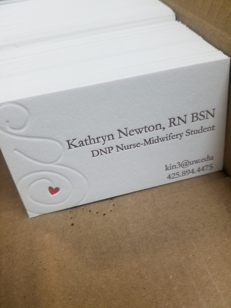 Photo shows a stack business cards in a large stack on its side. They are a business card for a midwifery student. There is an image of a silhouette of a woman, with a red heart where the uterus/fetus would be.