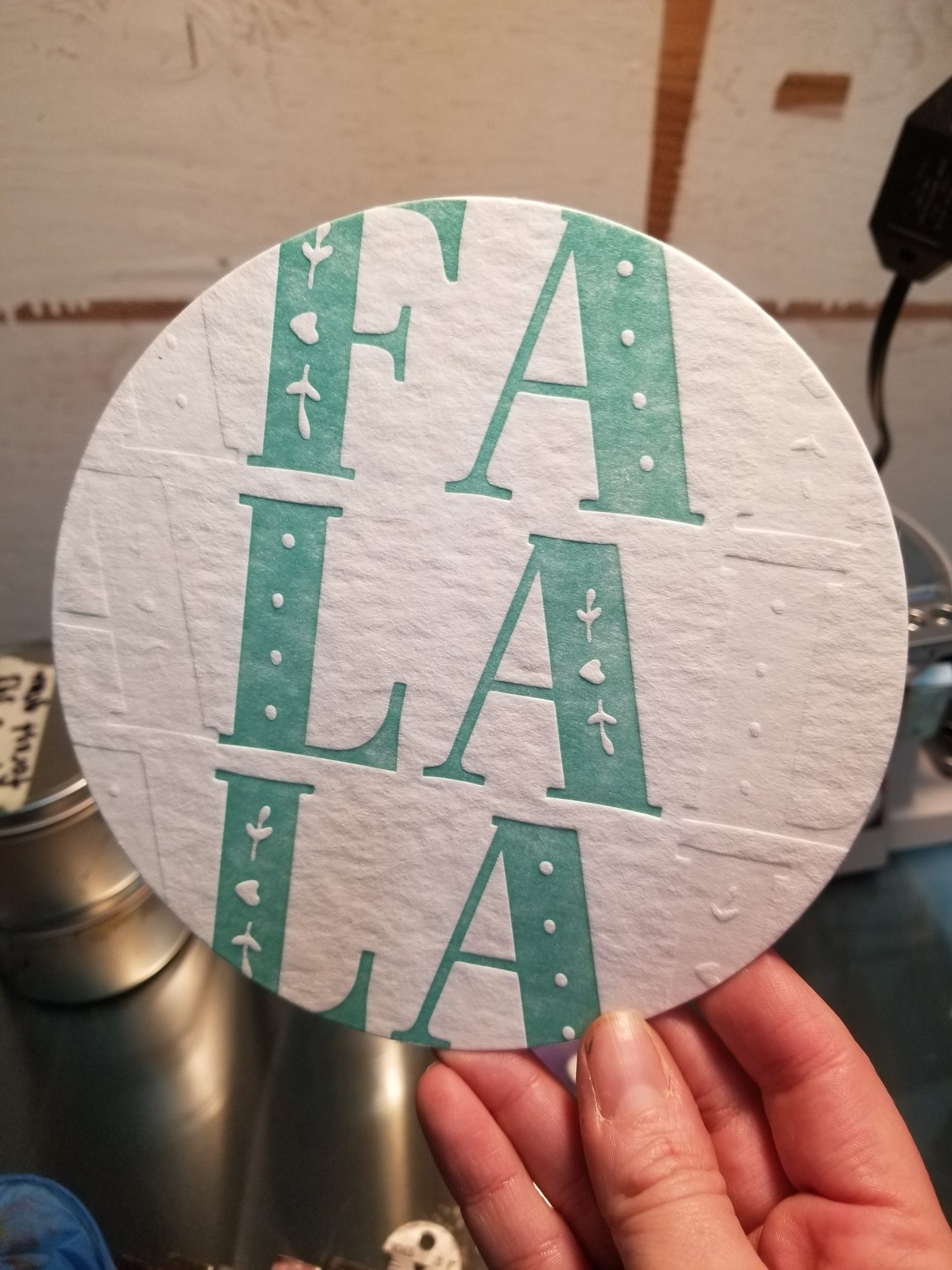 Photo shows a 6 inch diecut circle with the words FA LA LA printed in teal, down a row. There is a blind deboss to the left and right of the word, featuring the same text.
