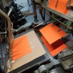 Photo shows orange paper being fed through the Kluge foil press.