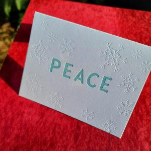 "Photo shows a letterpressed folding card that says ""PEACE"" in large, sans serif type in the center of the card, and it is surrounded by debossed snowflakes."