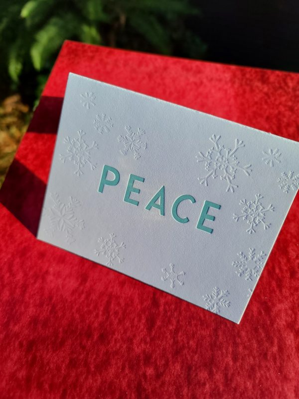 """Photo shows a letterpressed folding card that says """"PEACE"""" in large, sans serif type in the center of the card, and it is surrounded by debossed snowflakes."""