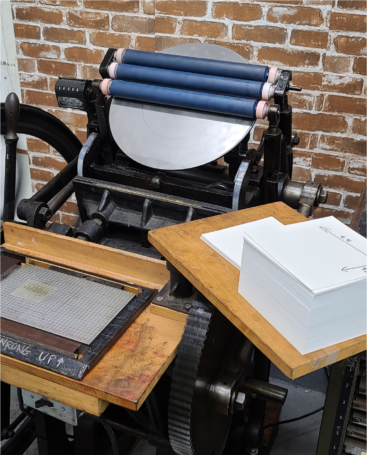 Image of a handfed Chandler and Price letterpress machine. Rollers are in the UP position, and there is a brick wall behind the press.